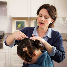 mom performing a do it yourself treatment for head lice